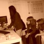 Ein Mädchen am Rechner, zwei Mädchen schauen zu